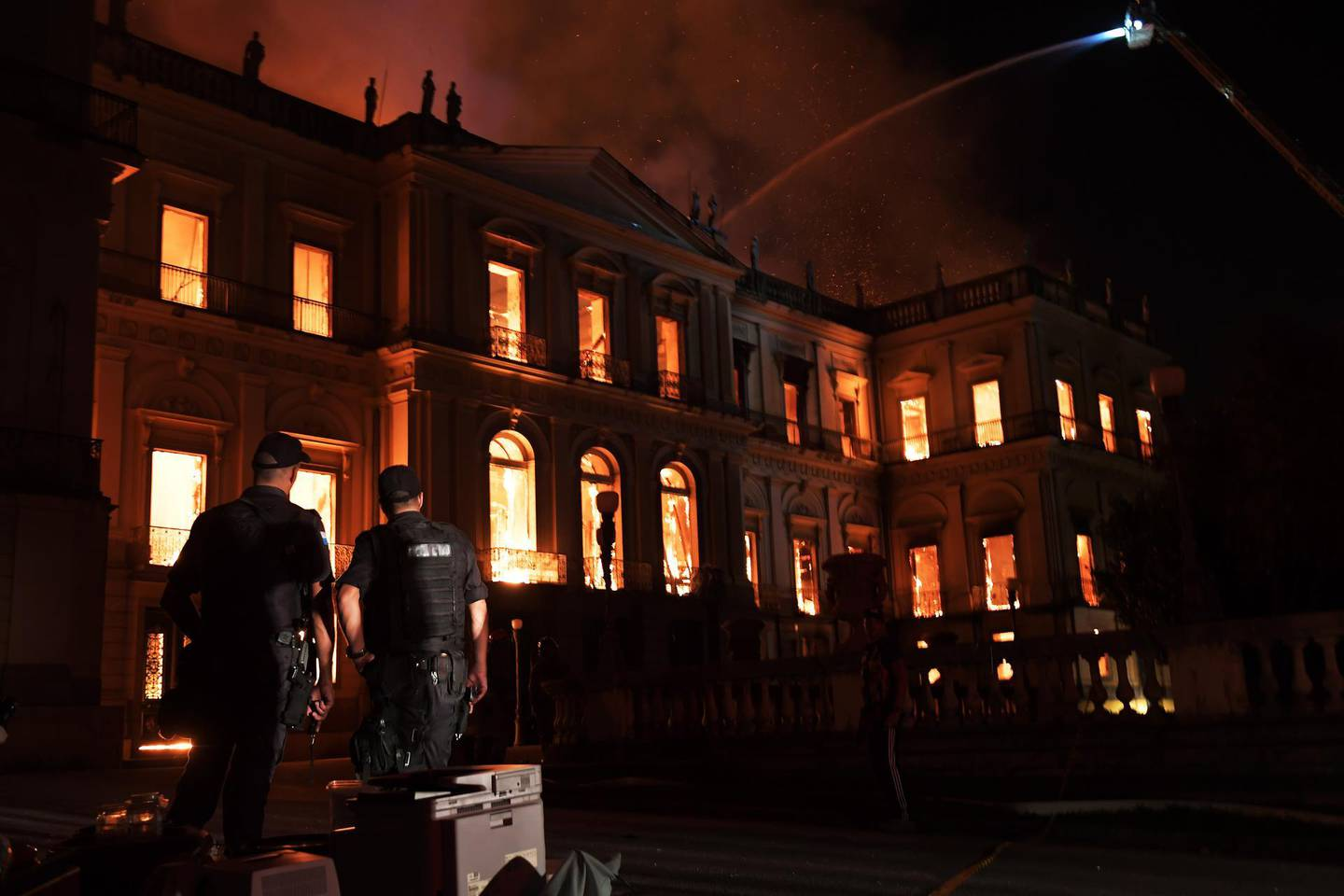 Policemen watch as a massive fire engulfs the National Museum in Rio de Janeiro, one of Brazil's oldest, on September 2, 2018. - The cause of the fire was not yet known, according to local media. (Photo by Carl DE SOUZA / AFP)