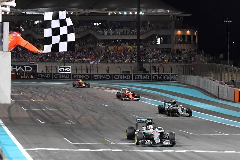 Mercedes AMG Petronas F1 Team's British driver Lewis Hamilton crosses the finish line at the end of the Abu Dhabi Formula One Grand Prix at the Yas Marina circuit on November 27, 2016. - Nico Rosberg won his maiden Formula One world title by securing second place behind his Mercedes arch-rival Lewis Hamilton in the Abu Dhabi Grand Prix. (Photo by Andrej ISAKOVIC / AFP)