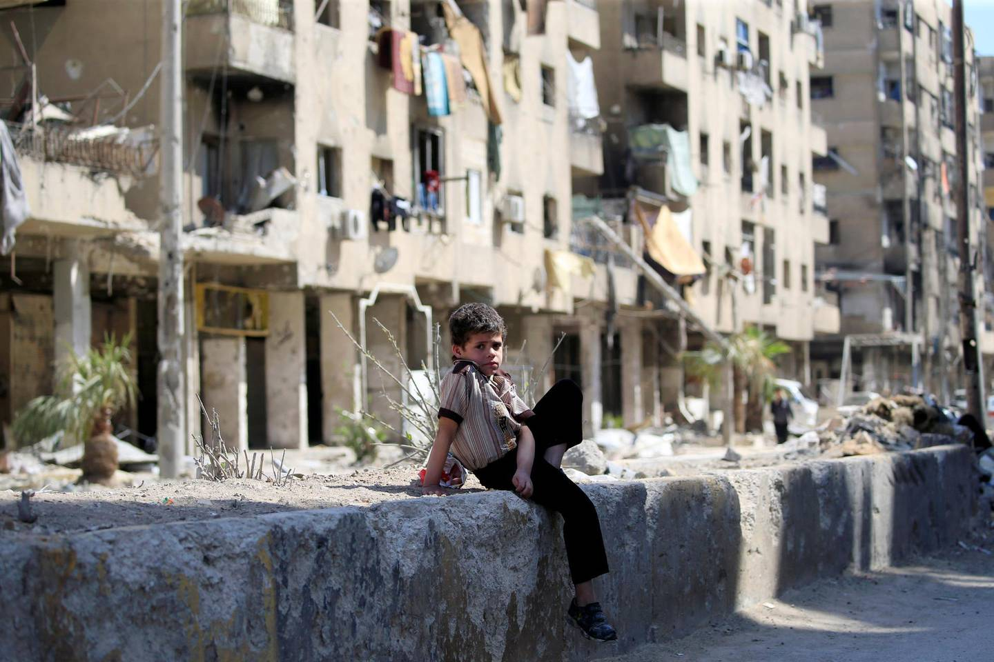 A child sits in a street during a media tour in Douma near Damascus, Syria April 23, 2018. REUTERS/ Ali Hashisho