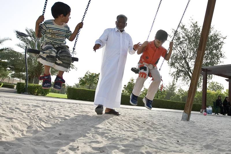 United Arab Emirates -Dubai- May 15, 2009:  HOUSE & HOME: Zubair Ali (cq-al), 53, center, pushes his nephews Houshad Haarith (cq-al), 3, left, and Al Haarith (cq-al), 6, right, on the swings of a playground in the Nad Al Sheba neighborhood in Dubai on Friday, May 15, 2009. Amy Leang/The National  *** Local Caption ***  amy_051509_nadalsheba_22.jpgamy_051509_nadalsheba_22.jpg