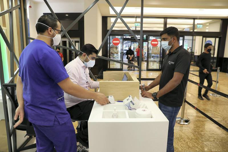 DUBAI, UNITED ARAB EMIRATES , October 14 – 2020 :- Anto Antony (right) taking the token for his COVID-19 nasal swab test at the COVID 19 testing station set up at Mall of the Emirates in Dubai. (Pawan Singh / The National) For News/Online. Story by Sarwat
