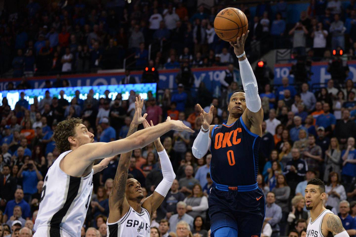 Dec 3, 2017; Oklahoma City, OK, USA; Oklahoma City Thunder guard Russell Westbrook (0) drives to the basket in front of San Antonio Spurs center Pau Gasol (16) and guard Dejounte Murray (5) during the first quarter at Chesapeake Energy Arena. Mandatory Credit: Mark D. Smith-USA TODAY Sports