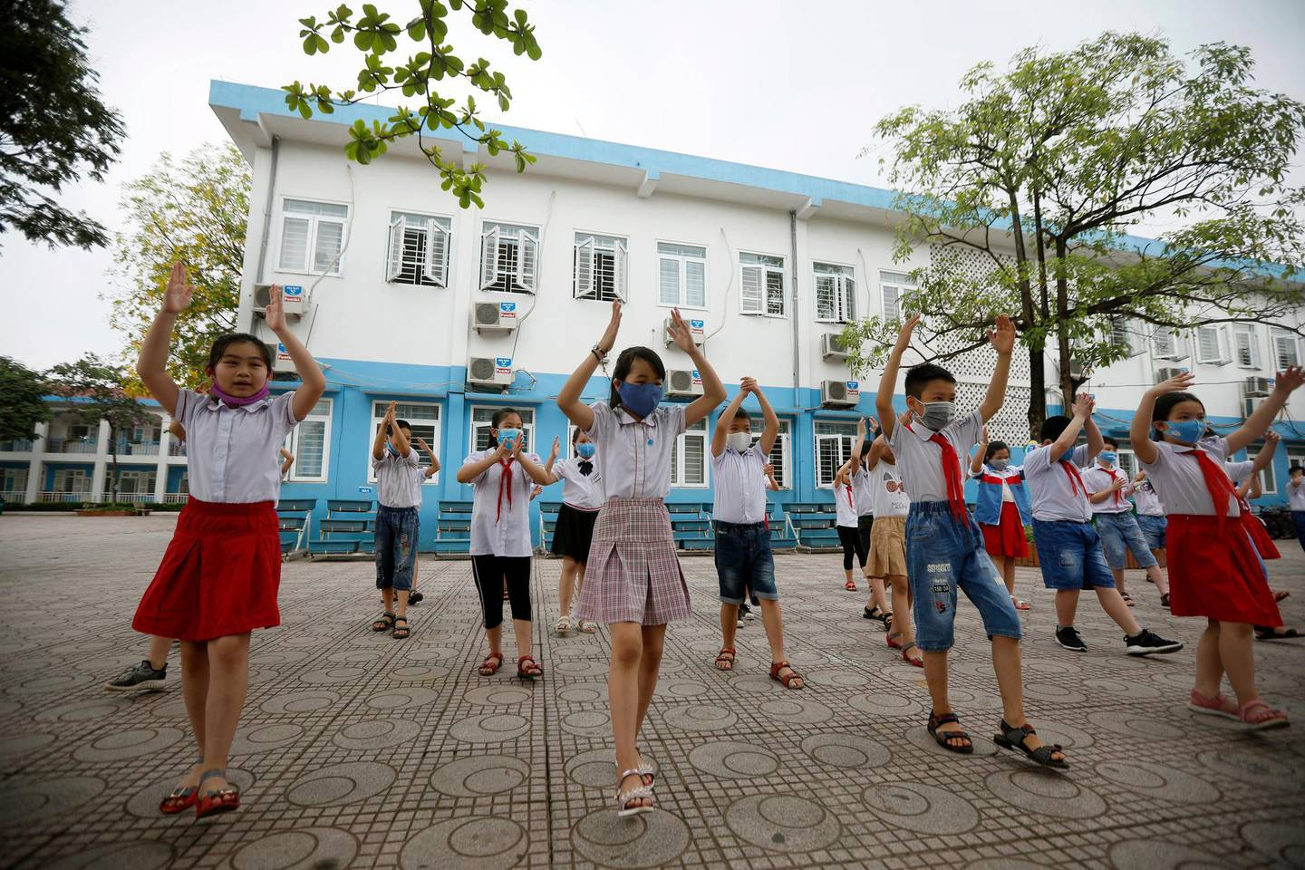 epa08415272 Children do gymnastic exercise in Phuc Dien elementary school Hanoi, Vietnam, 11 May 2020. Young children from kindergarten and elementary school across the country have returned to school after a three-month closure due to the COVID-19 disease pandemic.  EPA/LUONG THAI LINH