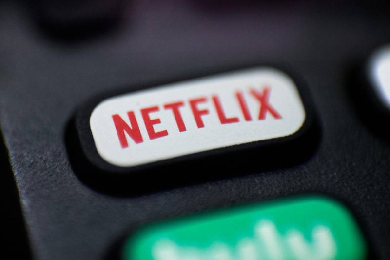 FILE - This Aug. 13, 2020, file photo shows a logo for Netflix on a remote control in Portland, Ore. Netflix's video streaming service has surpassed 200 million subscribers for the first time as its expanding line-up of TV series and movies continues to captivate people stuck at home during the ongoing battle against the pandemic. The subscriber milestone highlighted Netflix's fourth-quarter results released Tuesday, Jan. 19, 2021. (AP Photo/Jenny Kane, File)