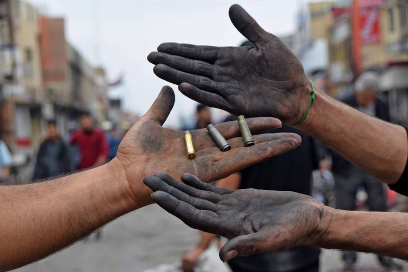 This picture taken on November 28, 2020 shows two men holding up spent bullet casings found at a protest site in Habboubi Square in Iraq's southern city of Nasiriyah in Dhi Qar province. Anti-government protesters defied lockdowns and the threat of violence to demonstrate on November 28 in several Iraqi cities. In the southern hotspot of Nasiriyah, anti-government activists accused supporters of populist Shiite cleric Moqtada Sadr of shooting at them and torching their tents in their main gathering place of Habboubi Square late the day before. Nasiriyah was a major hub for the protest movement that erupted last year against a government seen by demonstrators as corrupt, inept and beholden to neighbouring Iran. / AFP / Asaad NIAZI