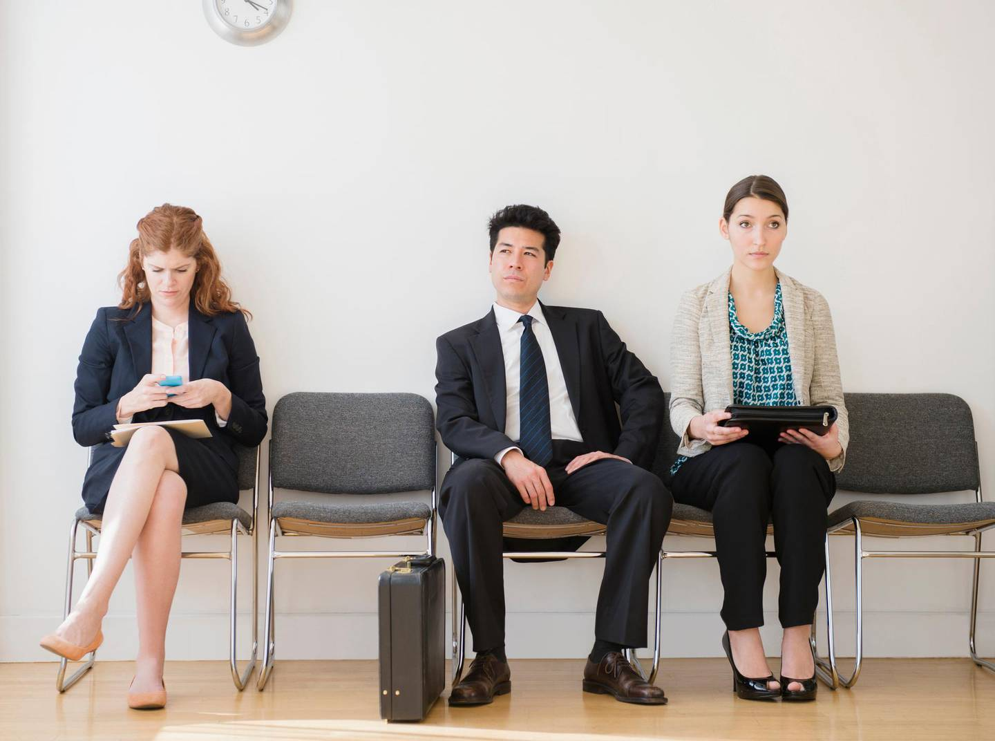 Business people in office waiting room. Getty Images
