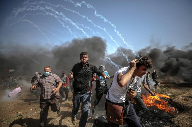 epa06795301 Palestinians protesters run for cover from Israeli tear-gas during the clashes after Friday protest near the border east Gaza City on, 08 June 2018. Reports state that a twelve year old boy and other three Palestinians were killed and more than 600 protesters were wounded during the clashes near the border eastern Gaza Strip. Protesters plan to call for the right of Palestinian refugees across the Middle East to return to homes they fled in the war surrounding the 1948 creation of Israel.  EPA/MOHAMMED SABER