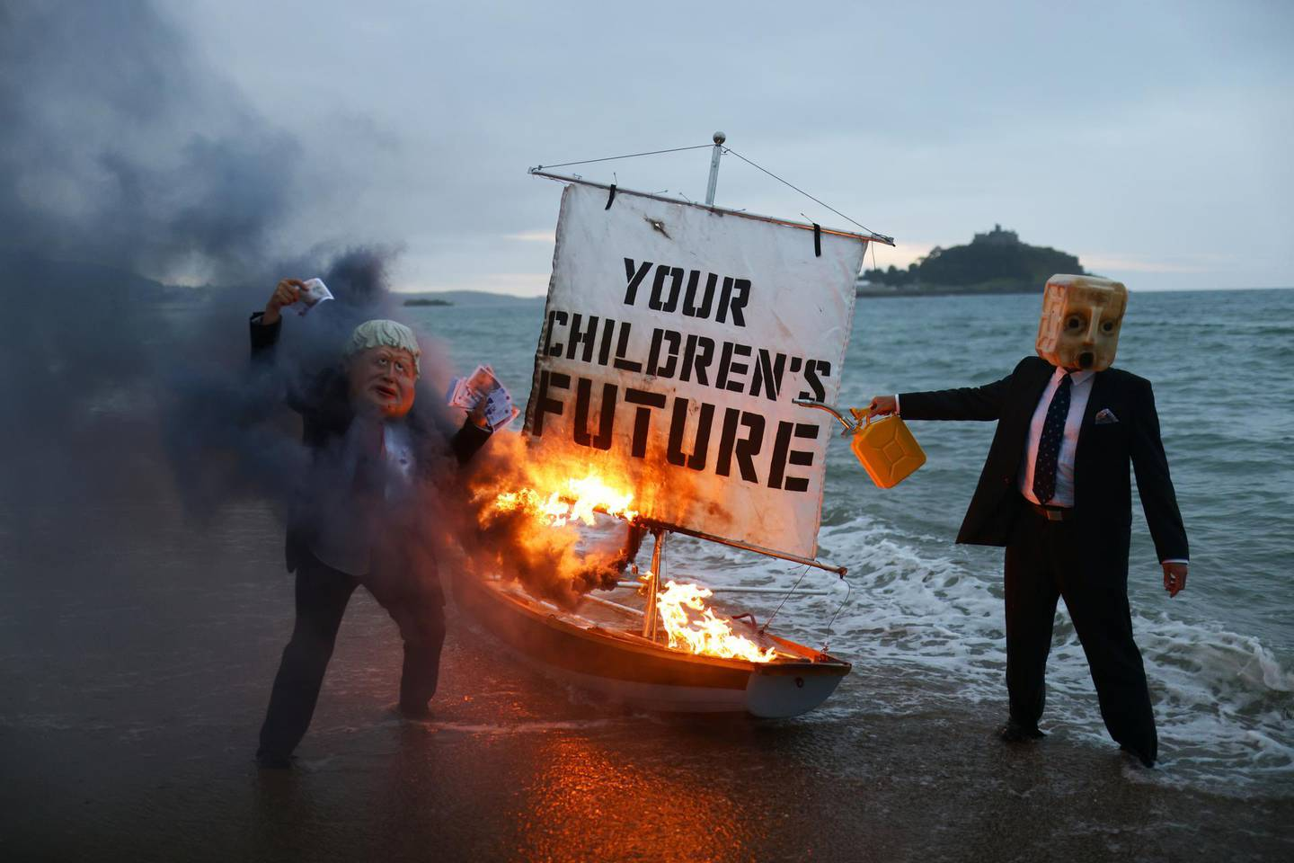 Activists from climate action group Ocean Rebellion set a boat on fire during a demonstration at sunrise at Marazion Beach, Cornwall, Britain, June 5, 2021, ahead of the G7 summit in Carbis Bay, Cornwall. REUTERS/Tom Nicholson