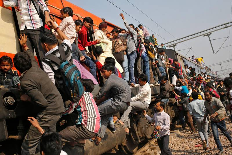 Passengers board an overcrowded train near a railway station at Loni town in the northern state of Uttar Pradesh, India, February 24, 2016. India's federal-run railways will have to depend on more government support and borrowing to fix their finances in its budget on Thursday, with New Delhi reluctant to unveil steep fare hikes ahead of key state elections, officials said. REUTERS/Anindito Mukherjee - D1AESOWIOAAA