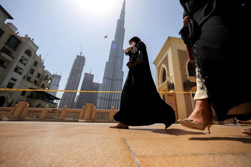 Women walk past the Burj Khalifa in Dubai, United Arab Emirates, June 11, 2021. Picture taken June 11, 2021. REUTERS/Christopher Pike