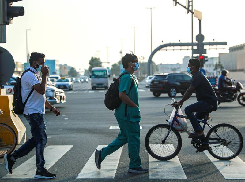 Abu Dhabi, United Arab Emirates, March 7, 2021. Pedestrians cross the street at central Abu Dhabi on a hazy afternoon.one of the students who has taken the course Victor Besa / The NationalSection:  NAFor:  Stock Covid/Weather