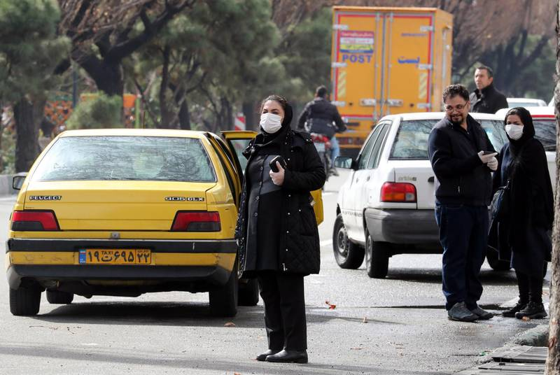 epa08250955 Iranians wearing face masks wait for taxi on a street of Tehran, Iran, 26 February 2020. According to the Ministry of Health, 139 people diagnosed with the Covid-19 coronavirus and 19 people have died in Iran.  EPA/ABEDIN TAHERKENAREH