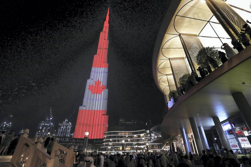 DUBAI ,  UNITED ARAB EMIRATES , JULY 1 – 2019 :- People gathered to see Burj Khalifa which is displaying a projection of the Canada Flag on the Canadian National Day at Dubai Mall in Dubai. ( Pawan Singh / The National ) For News