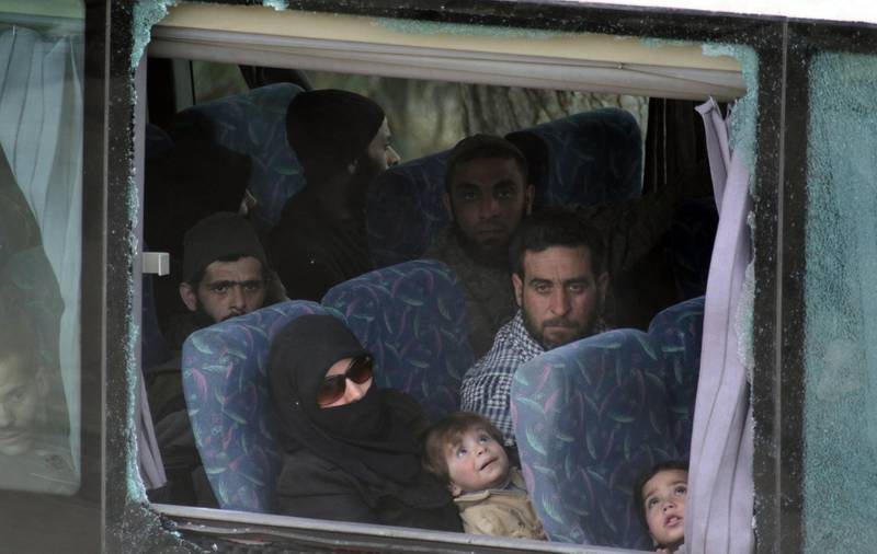 epa06625214 People sit in a government chartered coach carrying fighters and their families from the besieged city of Harasta are on their way to the northwestern city of Idlib, Syria, 23 March 2018 in accordance with an agreement with the Syrian government to surrender in exchange for getting safe way to Idlib. According to media reports, some 50 coaches left Harasta on 23 March 2018 with 2,806 on board, including 990 gunmen and 111 leaders of armed groups. The reports said that there were 10 busses remaining to complete the evacuation process and declare Harasta as a city free of armed presence.  EPA/YOUSSEF BADAWI