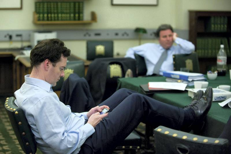 LONDON - MAY 10:  In this handout image provided by the Conservative Party, George Osborne checks his Blackberry in David Cameron's office in Portcullis House in the early hours of Monday morning as talks with the Liberal Democrats to form a coalition government continue on May 10, 2010 in London, England.  (Photo By Andrew Parsons/Conservative Party via Getty Images)