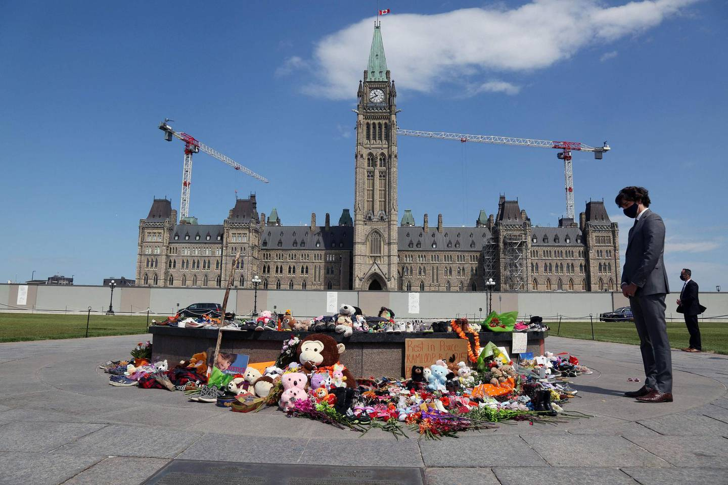 """Canadian Prime Minister Justin Trudeau visits the makeshift memorial erected in honor of the 215 indigenous children remains found at a boarding school in British Columbia, on Parliament Hill June 1, 2021 in Ottawa.   Trudeau, who has made reconciliation with Canada's nearly 1.7 million indigenous people a priority of his government since coming to power in 2015, said he would speak with his ministers to shore up """"next and further things we need to do to support (residential school) survivors and the community."""" / AFP / Dave Chan"""