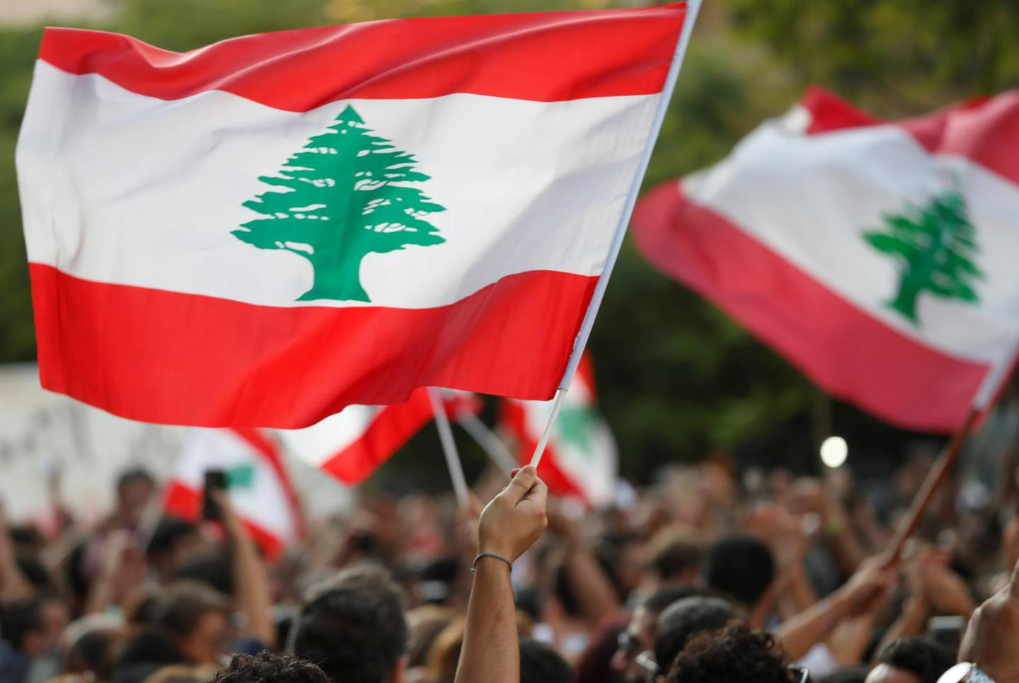 FILE PHOTO: Demonstrators wave Lebanese flags during a protest in Beirut, Lebanon, October 31, 2019. REUTERS/Goran Tomasevic/File Photo