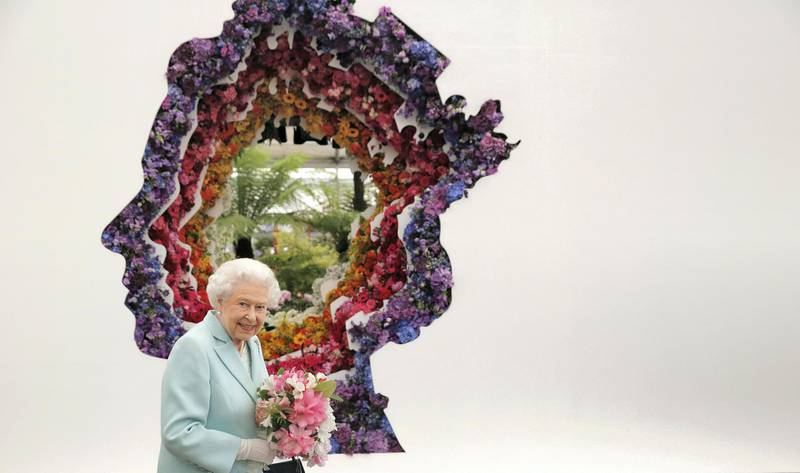 LONDON, ENGLAND - MAY 23:  Queen Elizabeth II is pictured next to a floral exhibit by the New Covent Garden Flower Market, which features an image of the Queen, at Chelsea Flower Show press day at Royal Hospital Chelsea on May 23, 2016 in London, England. The show, which has run annually since 1913 in the grounds of the Royal Hospital Chelsea, is open to the public from 24-28 May.  (Photo by Adrian Dennis - WP Pool/Getty Images)