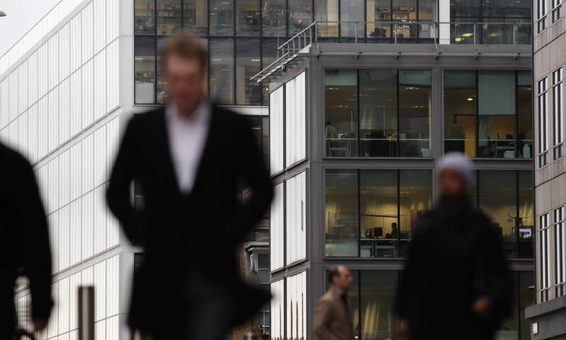 """LONDON, ENGLAND - JANUARY 11:  City workers walk past office buildings near Liverpool Street Station on January 11, 2011 in London, England. The Government has indicated that it could not """"micromanage"""" banks, suggesting that the campaign to reduce the latest bankers bonuses has failed. After warnings from the Prime Minister, the Royal Bank of Scotland and Lloyds TSB will be expected to announce the lowest payouts but even after evidence given to MPs today, Barclays chief executive, Bob Diamond is set to be awarded £8 million. (Photo by Dan Kitwood/Getty Images)"""