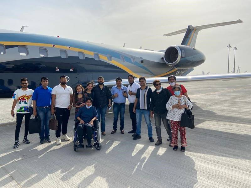 Dr Rahul Gupta (fourth from right) and Dr Rekha Singh (in a wheelchair) are among 13 UAE residents who returned from India recently on a business jet paying $43,000 after incoming commercial flights were suspended from India. Flights from India have been stopped to guard against a deadly Covid-19 strain. Courtesy: Dr Gupta