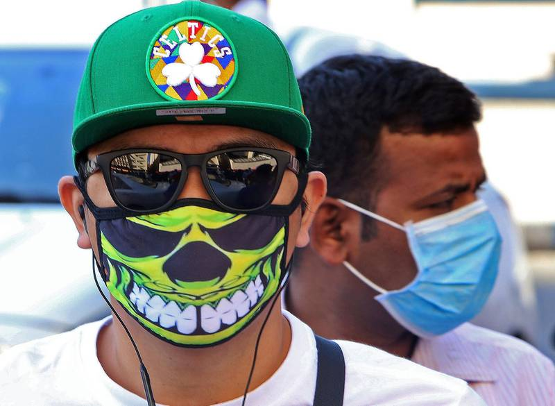 People wearing protective masks are seen on a street in Kuwait City on March 2, 2020, amid a global outbreak of the novel Coronavirus. / AFP / YASSER AL-ZAYYAT