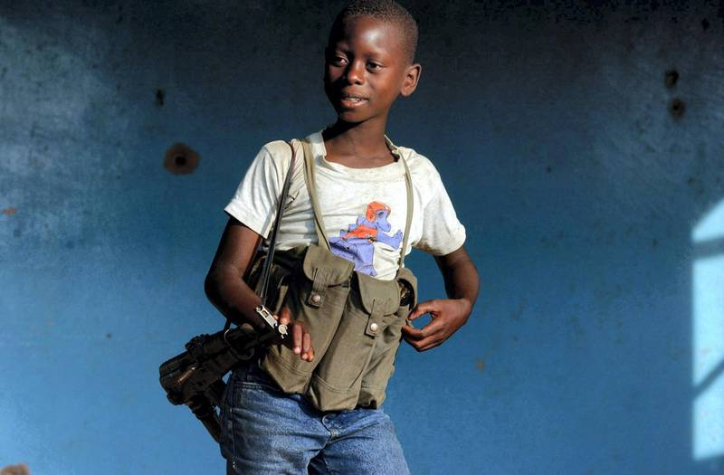 epa02576447 (FILE) A file picture dated 16 June 2003 shows a young child soldier who would not give his age to journalists in an ethnic Hema militia camp near Bunia in the Democratic Republic of Congo. On 12 February 2011 Red Hand Day will be observed worldwide through protest, demonstrations and other activities to raise awareness of the situation of child soldiers across the globe. Red Hand Day is takes place yearly on 12 February.  EPA/STEPHEN MORRISON *** Local Caption *** 02576447
