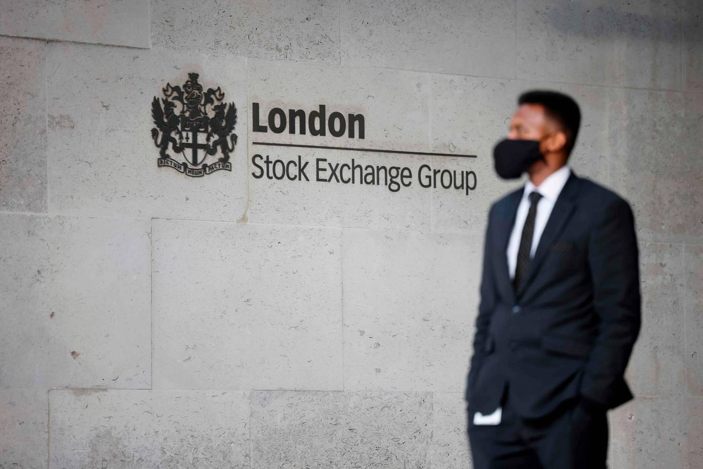 A security guard stands beside the logo for the London Stock Exchange Group outside the stock exchange in London on December 29, 2020. The London stock market soared on December 29 as investors gave their initial verdict on Britain's Brexit deal with the EU, while eurozone equities also rose on upbeat US stimulus news, with Frankfurt extending its record breaking run. / AFP / Tolga Akmen