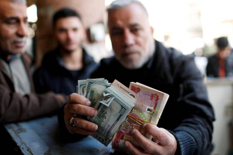 A man holds money as he poses for a picture at a foreign currency exchange market in Baghdad, Iraq, December 20, 2020. REUTERS/Thaier Al-Sudani