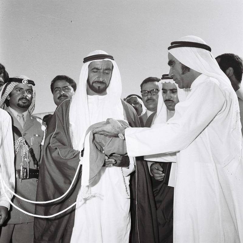 """History Project 2010, """"The First Day"""". Sheikh Zayed raising the flag at Union House in Dubai. December 2, 1971. Mahdi Tajer (right, need to confirm this) is shown handing the flag to Sheikh Zayed. Credit Ittihad Newspaper **EDS NOTE ***IMPORTANT** SEEK ADVISE FROM KAREN BEFORE USE"""