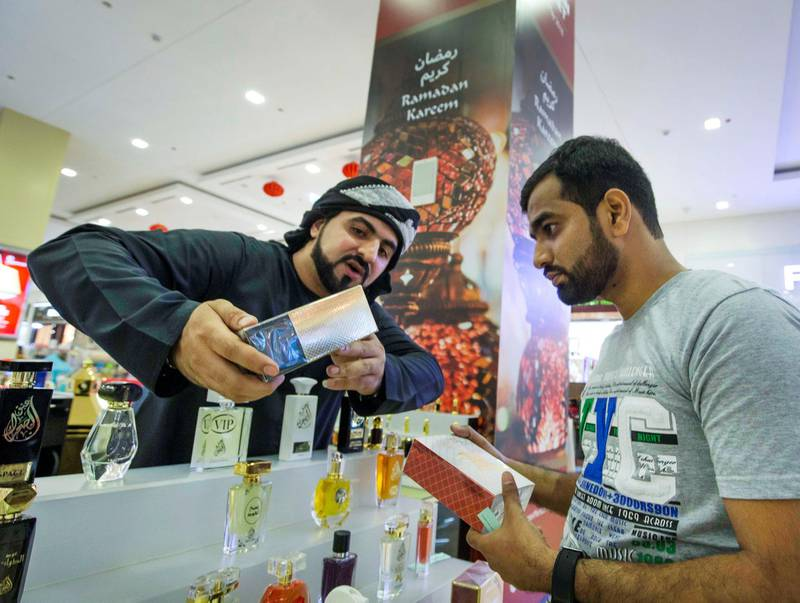 DUBAI, UNITED ARAB EMIRATES, 04 May 2018 - A salesman showing his perfume products to a shopper at Ramadan Market that opens May 3 till 19 at  Dragon Mart 2.  Leslie Pableo for The National for Ellen Fortini's story