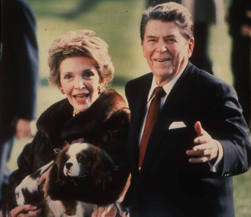 """Mandatory Credit: Photo by Dennis Cook/AP/Shutterstock (11087592a)First lady Nancy Reagan holding the Reagans' pet Rex, a King Charles spaniel, as she and President Reagan walk on the White House South lawn. The arrival of the Biden pets will also mark the next chapter in a long history of pets residing at the White House after a four-year hiatus during the Trump administration. """"Pets have always played an important role in the White House throughout the decades,"""" said Jennifer Pickens, an author who studies White House traditionsWhite House Pets, Washington, United States - 01 Dec 1986"""