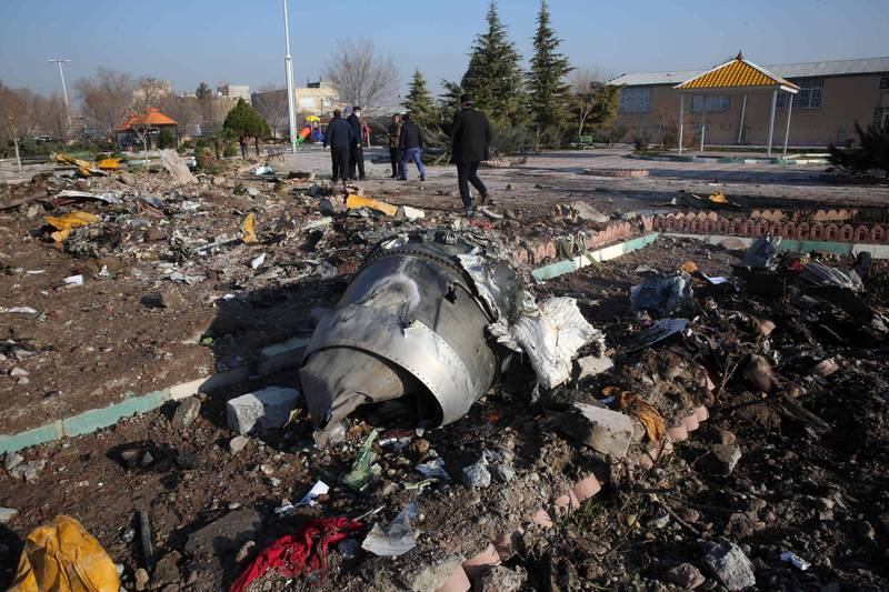 """(FILES) In this file photo rescue teams work amidst debris after a Ukrainian plane carrying 176 passengers crashed near Imam Khomeini airport in the Iranian capital Tehran early in the morning on January 8, 2020, killing everyone on board. Canada said it was demanding answers from Iran over the mistaken downing of a Ukrainian passenger jet after Tehran's """"limited"""" initial report failed to explain why it fired missiles at the plane. Ukraine International Airlines Flight 752 crashed shortly after taking off from Tehran's main airport on January 8. Iran admitted days later that its forces had accidentally shot down the Kiev-bound Boeing 737-800, killing all 176 people on board, including 55 Canadians.The Canadian government said August 23, 2020 it had received a copy of the Iranian report on the cockpit voice recorders.  / AFP / -"""