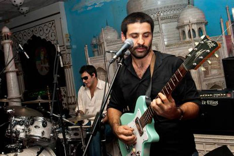 """(FILES)--A November 2 2007, file photo shows Lebanese singer Zeid Hamdan playing his guitar at the Maharaja restaurant in Beirut. Hamdan, 35-years-old, was detained on July 27, 2011, for slandering Lebanon's head of state in a song posted on YouTube in which he urges President Michel Sleiman to """"go home,"""" his attorney told AFP. AFP PHOTO/GHADI SMAT"""