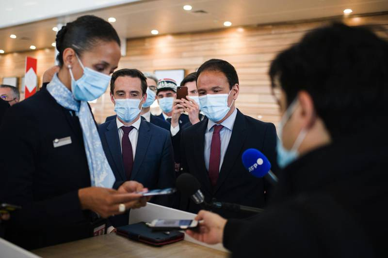 Jean-Baptiste Djebbari, France's transport minister, second left, and Cedric O., France's digital affairs minister, second right, watch Air France-KLM check-in staff demonstrating the 'TousAntiCovid' Coronavirus smartphone tracing app at Orly Airport in Paris, France, on Tuesday, April 27, 2021. France is moving toward a broad rollout of digital health certificates, putting the country at the forefront of a European Union push for vaccine passports to jumpstart travel. Photographer: Nathan Laine/Bloomberg