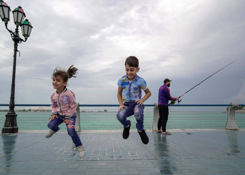 Abu Dhabi, United Arab Emirates, November 20, 2019.   UAE weather: rainfall and storms arrive as all schools close.--  Huda and Bakr Kaaki enjoy the cool weather and missing class today due to the rains and stormy weather on a stroll along the Corniche with their mother and grandmother.Victor Besa / The NationalSection:  NAReporter: