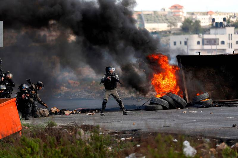 Israeli security forces take aim during clashes with Palestinian demonstrators following a demonstration in the West Bank city of Ramallah on March 16, 2018, as protests continue in the region amid anger over US President Donald Trump's recognition of Jerusalem as its capital.  / AFP PHOTO / ABBAS MOMANI