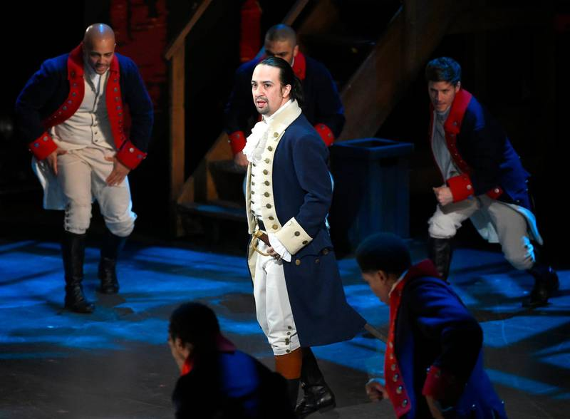 """FILE - In this June 12, 2016 file photo, Lin-Manuel Miranda and the cast of """"Hamilton"""" perform at the Tony Awards in New York.  Next year, you'll be able to see the original Broadway cast of """"Hamilton"""" perform the musical smash from the comfort of a movie theater. The Walt Disney Company said Monday, Feb. 3, 2020, it will distribute a live capture of Lin-Manuel Miranda's show in the United States and Canada on Oct. 15, 2021. (Photo by Evan Agostini/Invision/AP, File)"""