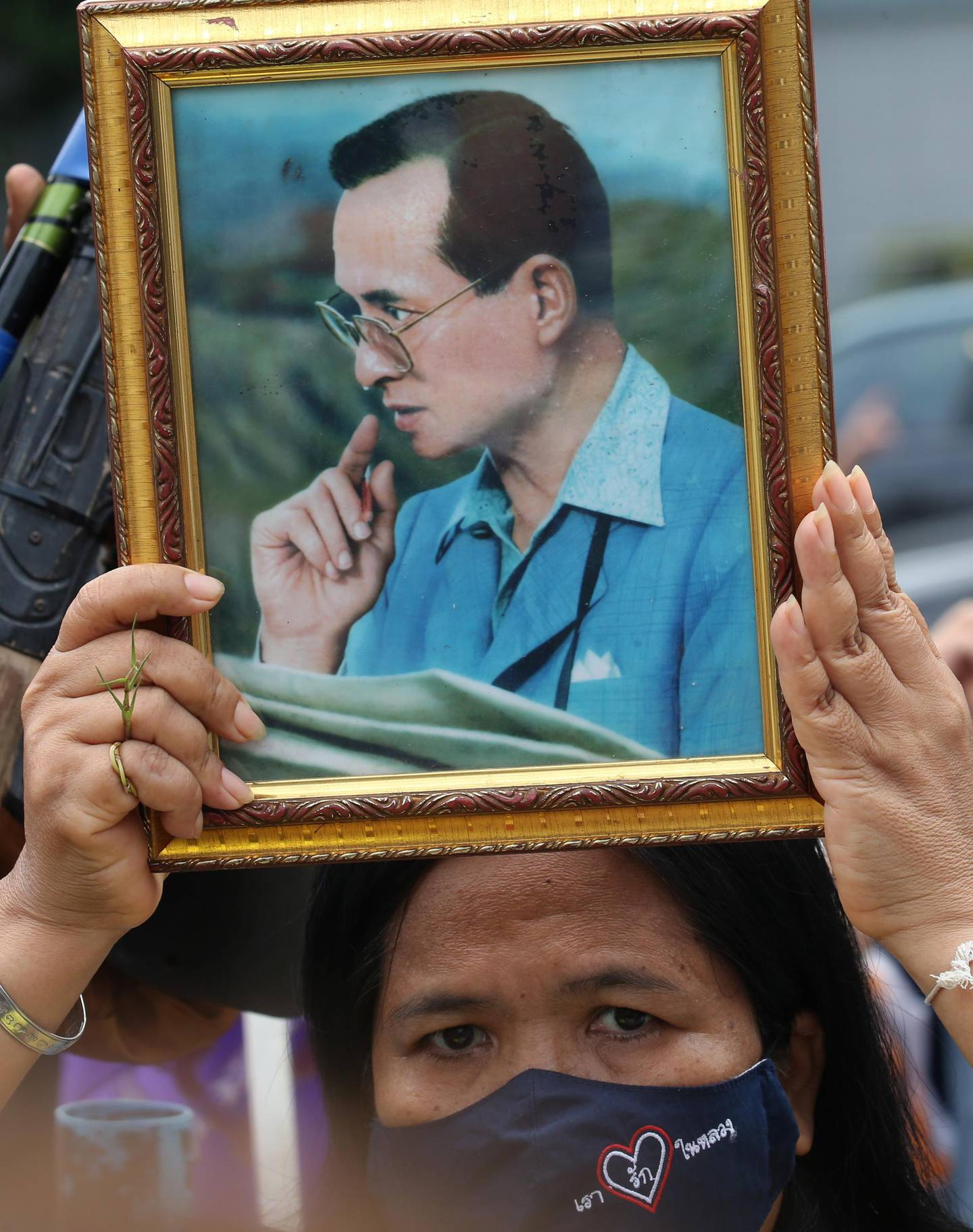epa08689765 A Royalist and pro-government supporter holds a photograph of the late Thai King Bhumibol Adulyadej, during a rally held to show opposition to any amendments to the constitution, outside the Parliament House, in Bangkok, Thailand, 23 September 2020. The parliament of Thailand will hold special sessions from 23 to 24 September 2020 to deliberate charter amendment proposals and the establishment of a charter drafting group.  EPA/NARONG SANGNAK