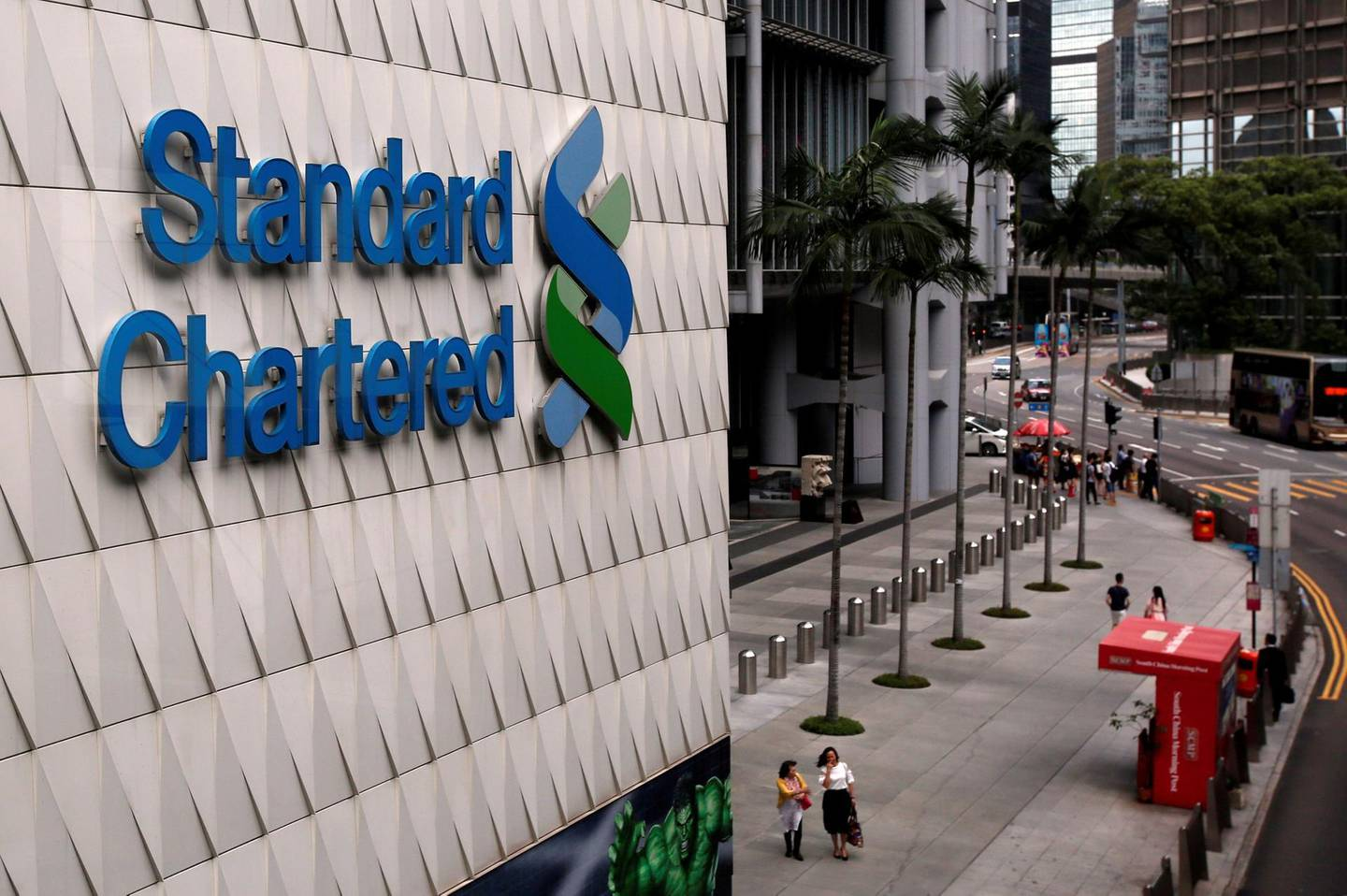 FILE PHOTO: People walk outside the main branch of Standard Chartered in Hong Kong, China August 1, 2017. REUTERS/Bobby Yip/File Photo