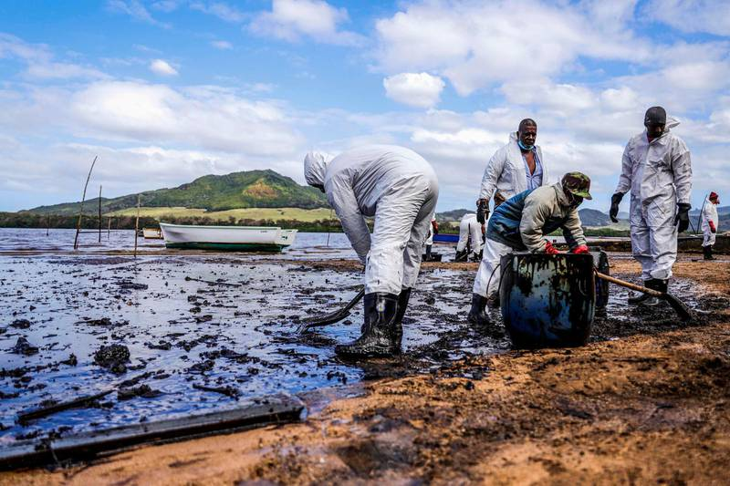 TOPSHOT - People scoop leaked oil from the vessel MV Wakashio, belonging to a Japanese company but Panamanian-flagged, that ran aground and caused oil leakage near Blue bay Marine Park in southeast Mauritius on August 9, 2020. France on August 8, 2020 dispatched aircraft and technical advisers from Reunion to Mauritius after the prime minister appealed for urgent assistance to contain a worsening oil spill polluting the island nation's famed reefs, lagoons and oceans. Rough seas have hampered efforts to stop fuel leaking from the bulk carrier MV Wakashio, which ran aground two weeks ago, and is staining pristine waters in an ecologically protected marine area off the south-east coast. / AFP / L'Express Maurice / Daren Mauree