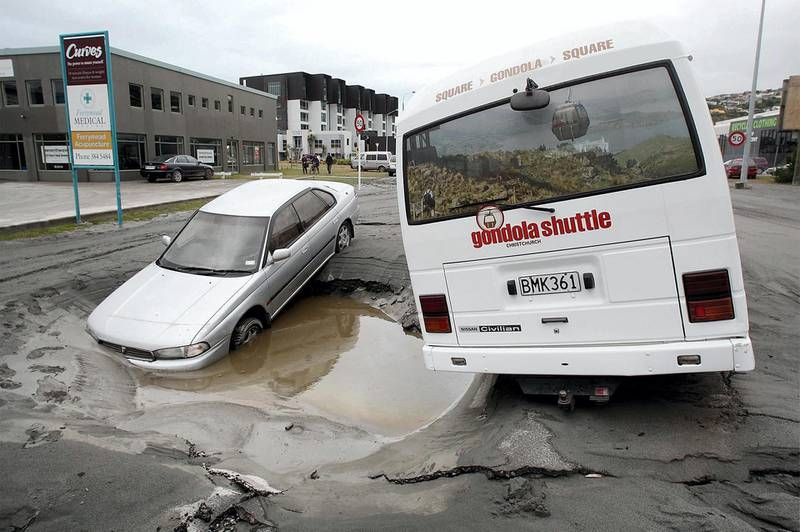 Vehicles trapped in a hole in the road on February 23, 2011, a day after a deadly 6.3 magnitude earthquake rocked the city of Christchurch. AFP