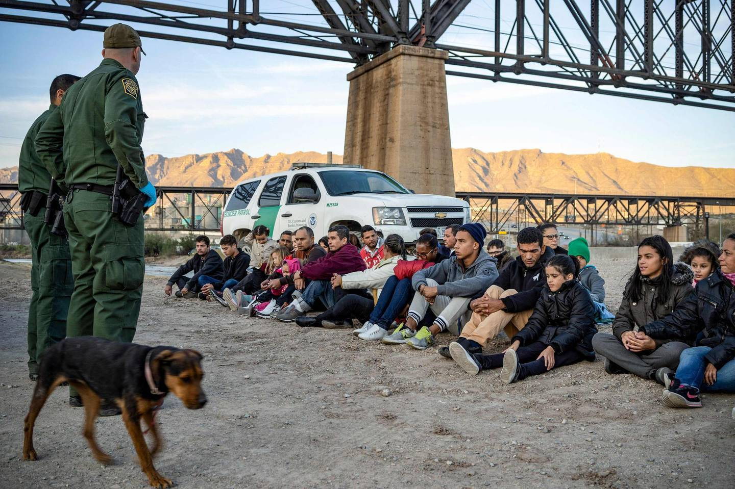 (FILES) In this file photo a group of about 30 Brazilian migrants, who had just crossed the border, sit on the ground near US Border Patrol agents, on the property of Jeff Allen, who used to run a brick factory near Mt. Christo Rey on the US-Mexico border in Sunland Park, New Mexico on March 20, 2019.  The flow of migrants and trade, legal and illegal, across the US-Mexican border will be the focus on March 1, 2021 when President Joe Biden meets with counterpart Andres Manuel Lopez Labrador in a virtual summit. Their meeting comes as reports say the United States faces a new surge of undocumented migrants attempting to enter the country from its southern neighbor, as Biden eases the tough anti-immigration regime of predecessor Donald Trump.  / AFP / Paul Ratje
