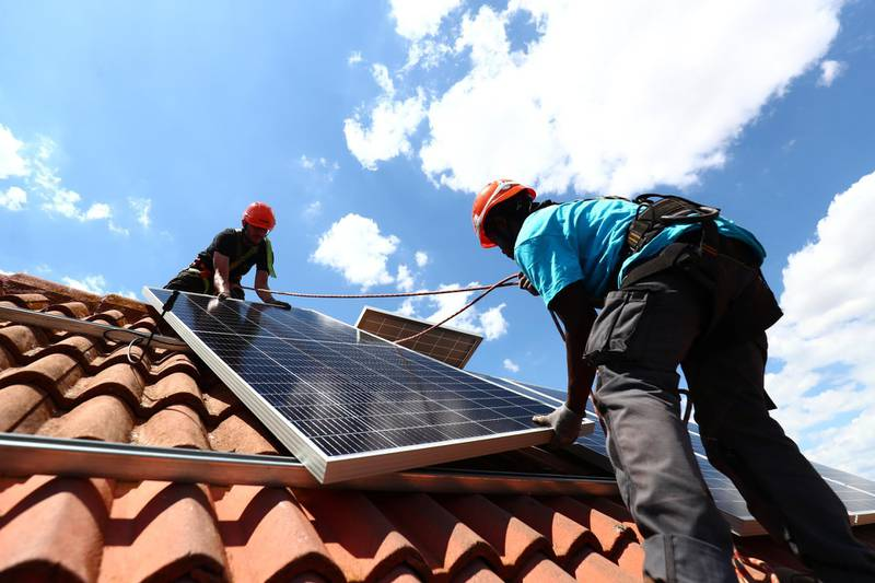 Rodrigue Kauahou and Jose Carlos Navarro, workers of the installation company Alromar, set up solar panels on the roof of a home in Colmenar Viejo, Spain June 19, 2020. Picture taken June 19, 2020. REUTERS/Sergio Perez