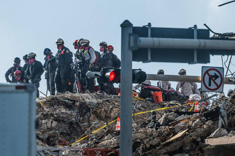 Search and Rescue teams look for possible survivors in the partially collapsed 12-story Champlain Towers South condo building on June 28, 2021 in Surfside, Florida. The death toll after the collapse of a Florida apartment tower rose to nine, officials said on June 27, 2021, with more than 150 people still missing and their weary families waiting nearly four days for information as to their fate.The outlook grew increasingly grim by the hour, however, as the slow rescue operation, involving workers sorting nonstop through the rubble in torrid heat and high humidity, carried on.  / AFP / Giorgio VIERA