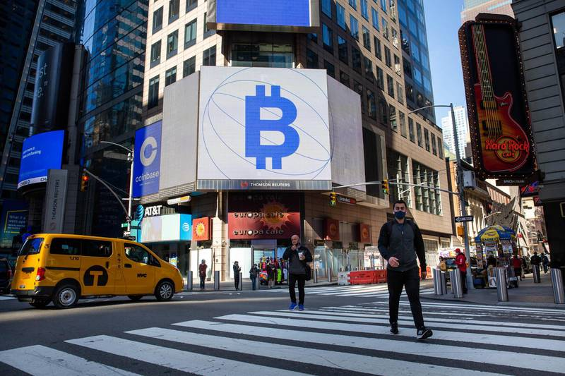 Monitors display Coinbase and Bitcoin signage during the company's initial public offering (IPO) at the Nasdaq MarketSite in New York, U.S., on Wednesday, April 14, 2021. Coinbase Global Inc., the largest U.S. cryptocurrency exchange, is set to debut on Wednesday through a direct listing, an alternative to a traditional initial public offering that has only been deployed a handful of times. Photographer: Michael Nagle/Bloomberg