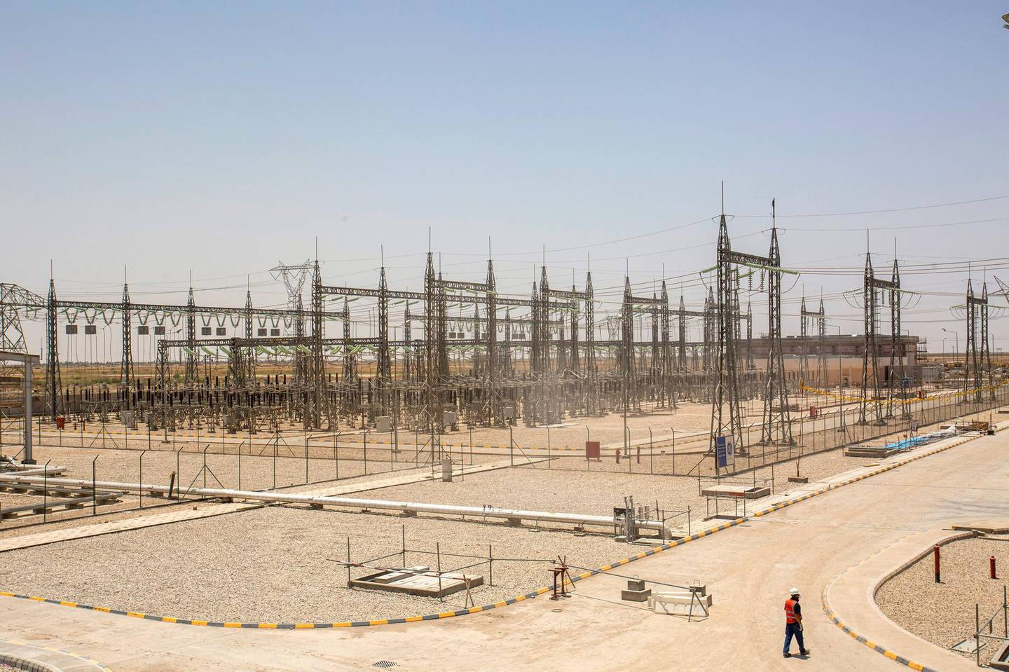An employee walks the ground of the Dhi Qar Combined Cycle Power Plant near the Iraqi city of Nasiriyah on June 15, 2020. (Photo by Hussein FALEH / AFP)