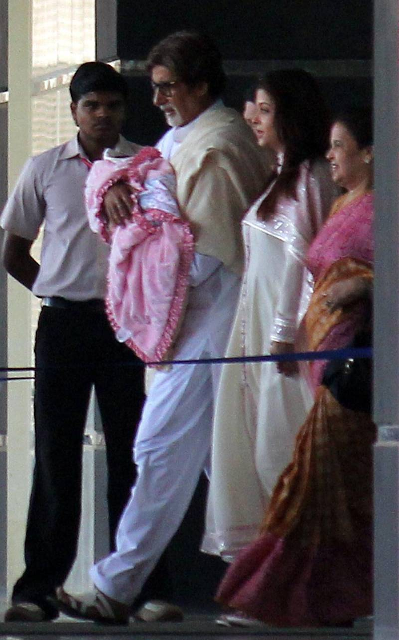 epa03011901 Bollywood actor Amitabh Bachchan (2-L) walks out of a hospital holding his grand-daughter along with his daughter-in-law Aishwarya Rai Bachchan (2-R), in Mumbai, India, 22 November 2011. Former Miss World and Bollywood actress Aishwarya Rai Bachchan, wife of Amitabh Bachchan's son, delivered the baby girl on 16 November 2011.  EPA/STR