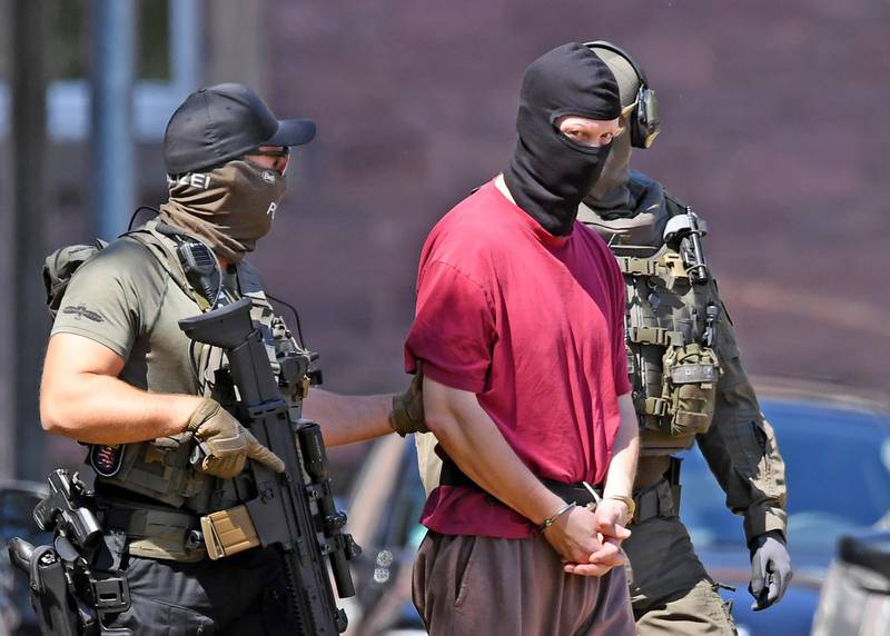 (FILES) In this file photo taken on July 02, 2019 Stephan E., supected of killing the administrative chief of the western city of Kassel Walter Luebcke, is escorted by police back to a helicopter after a hearing at the Federal Court of Justice in Karlsruhe, southern Germany.  A German neo-Nazi stands trial on June 15, 2020 on charges of murdering pro-refugee politician Walter Luebcke, the first political assassination since World War II that underscores a rising threat from extremism. - Germany OUT  / AFP / dpa / Uli Deck