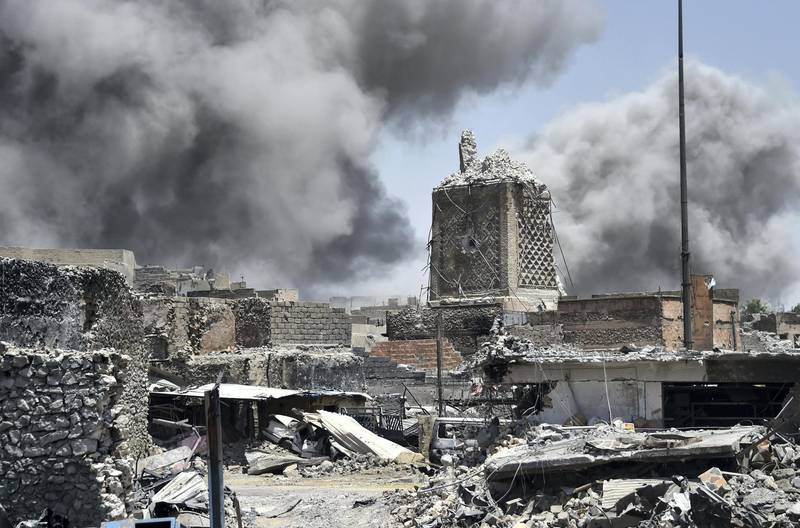 """Smoke billows in the background behind the base of Mosul's destroyed ancient leaning minaret, known as the """"Hadba"""" (Hunchback), in the Old City on June 30, 2017, after the area was retaken by the Iraqi forces from Islamic State (IS) group fighters.  Explosions on June 21 evening levelled the mosque, where Abu Bakr al-Baghdadi gave his first sermon as leader of the Islamic State group and its ancient minaret. - Iraq will declare victory in the eight-month battle to retake second city Mosul from jihadists in the """"next few days,"""" a senior commander said on June 30, 2017. Iraqi forces launched the gruelling battle for Mosul on October 17, 2016, advancing to the city and retaking its eastern side before setting their sights on the smaller but more densely populated west. (Photo by FADEL SENNA / AFP)"""