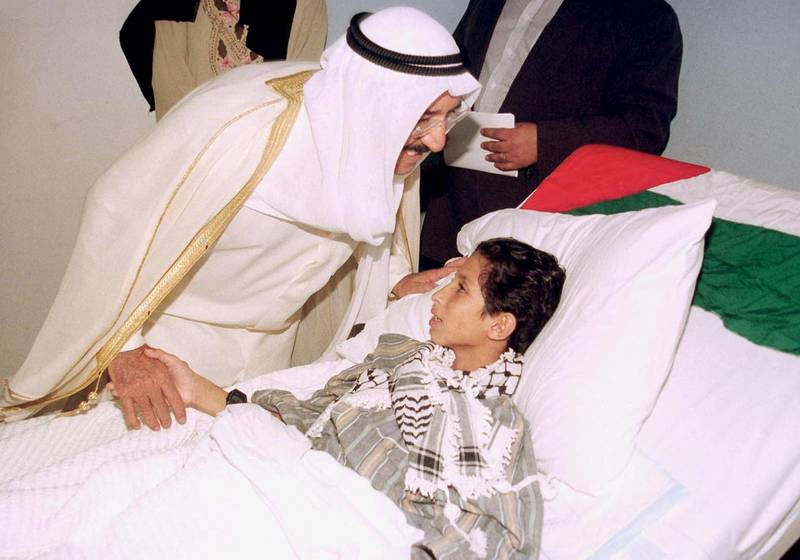 Kuwait Acting Prime Minister and Foreign Minister Sheikh Sabah al-Ahmad al-Sabah kisses a Palestinian boy, injured in clashes with Israeli forces, at a hospital 24 October 2000. Sheikh Sabah visited five Palestinians who arrived in Kuwait for medical care the previous day. (Photo by YASSER AL-ZAYYAT / AFP)